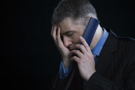 40 to 45 years old: Worried Businessman on the Telephone