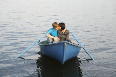 20 to 25 year olds: Young Couple Cuddling in Rowboat on Lake