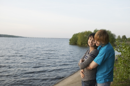 18 25 year old: Young Couple Cuddling on Lakeshore