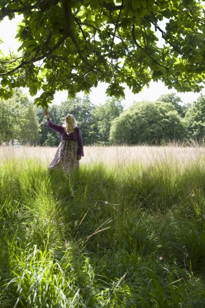 late fifties: Woman Standing Beneath a Tree