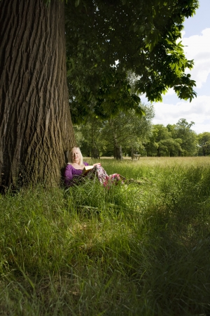 50 to 55 year olds: Woman Sitting Beneath a Tree Reading a Book