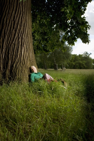 early fifties: Woman Sitting Beneath a Tree LANG_EVOIMAGES