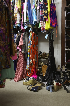 disorganization: Crowded Clothing Racks and Piled Shoes in Second Hand Store