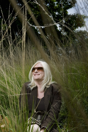 55 years old: Woman Sitting in Tall Grass LANG_EVOIMAGES