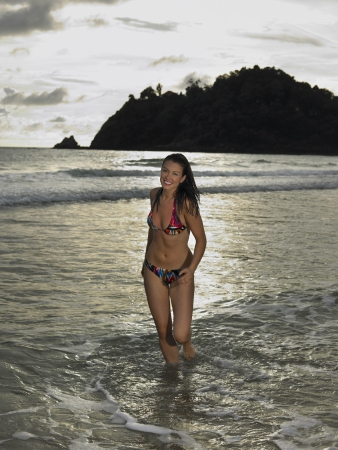 25 to 30 year olds: Young Woman Wading in Ocean at Sunset