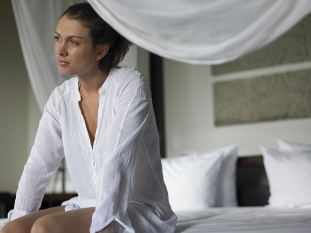 25 to 30 year olds: Young Woman in Shirt Sitting on Bed