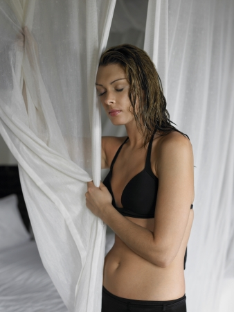 25 to 30 year olds: Young Woman in Bikini Holding Curtains
