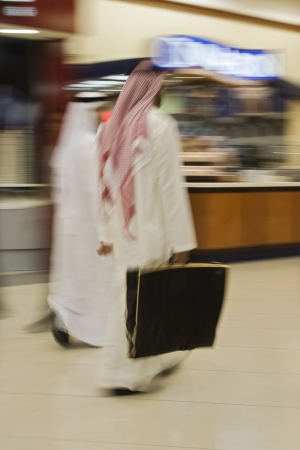 keffiyeh: Dubai UAE Two men traditionally dressed in dishdashs and gutras white robes and headdresses.