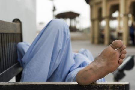 middle easterners: Dubai UAE man taking rest on park bench along boardwalk in Bur Dubai LANG_EVOIMAGES