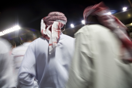 middle easterners: Dubai UAE small group of traditionally dressed Muslim men roaming grounds at Nad Al Sheba