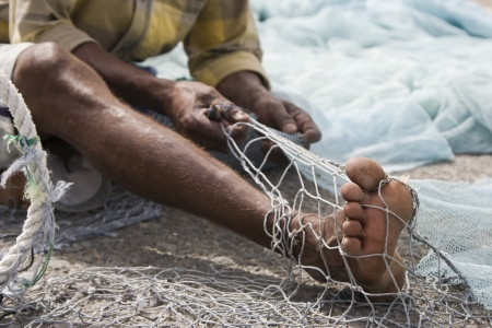middle easterners: Fujairah UAE A local fisherman fixes holes and tangles in his net in Fujairah.