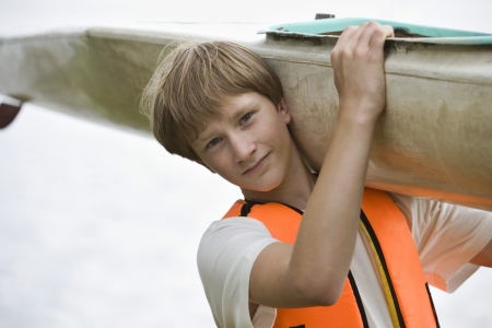 1 person: 18040001,Outdoors,Recreation,Adventure,Whites,Leisure Activities,One Person Only,Short Hair,Head And Shoulders,Sport,Teenage Boy,Blonde Hair,Holding,Carrying,one person,16-17 Years,Healthy Lifestyle,Looking At Camera,1 Person,Lifevest  ,