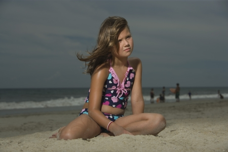 girl in sportswear: Little Girl Sitting on a Beach