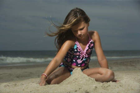 10 to 12 year olds: Little Girl Building a Sand Castle