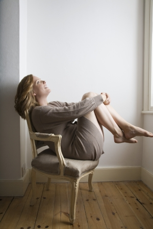 semi dress: Semi dress woman relaxing on old fashioned chair LANG_EVOIMAGES