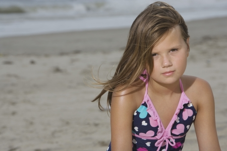 10 to 12 year olds: Little Girl Sitting on a Beach