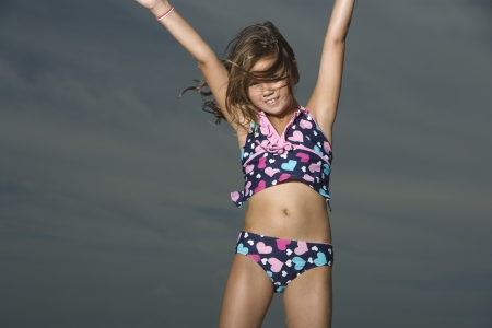 girl in sportswear: Little Girl in a Swimsuit Jumping