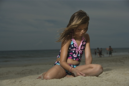 10 to 12 year olds: Sad Little Girl Sitting on a Beach