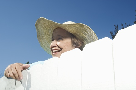 neighbour: Woman peering over garden fence LANG_EVOIMAGES