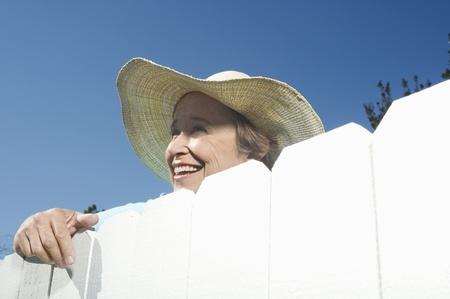 garden fence: Woman peering over garden fence LANG_EVOIMAGES