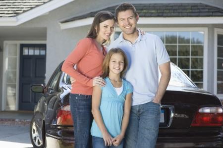 車と家の外の家族