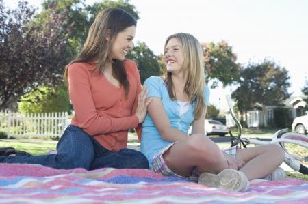 picnic blanket: Madre e hija sentada en una manta de picnic