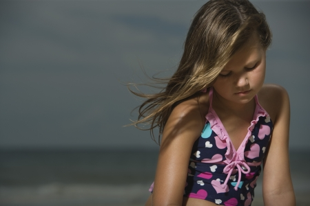 10 to 12 year olds: Sad Little Girl on a Beach
