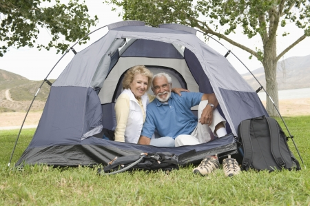 camping pitch: Senior couple at entrance to tent LANG_EVOIMAGES