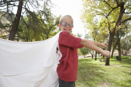 swimming goggles: Boy (7-9) wearing cape and swimming goggles LANG_EVOIMAGES