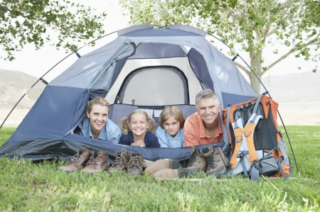 camping pitch: Family of four smiling from a tent