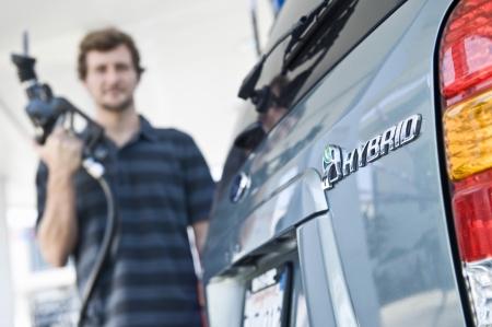 Man refueling hybrid car Imagens