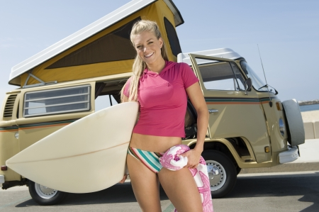 campervan: Young woman holding surfboard with camper van LANG_EVOIMAGES