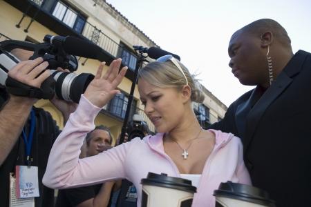 Female celebrity with bodyguard and paparazzi Stock Photo