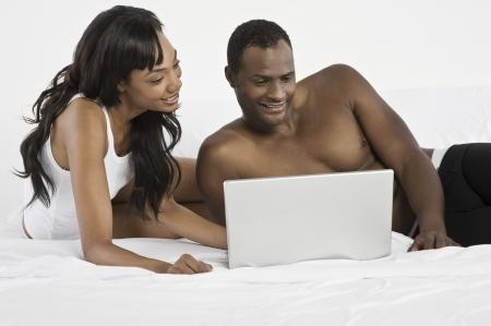 mid adult couple: Mediados de pares adultos usando la computadora port�til en el dormitorio