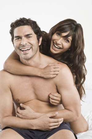 mid adult couple: Mid adult couple being playful in bed LANG_EVOIMAGES