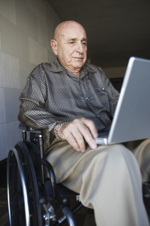 only 1 person: Elderly man in wheelchair using laptop LANG_EVOIMAGES
