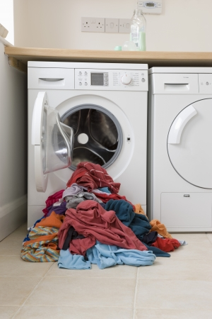 drudgery: Pile of clothes in front of washing machine