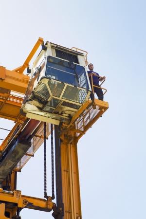 unknown age: Limassol Cyprus Operator having a break on gantry of mobile crane