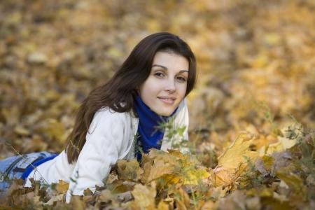 str: Woman lying on leaves in park