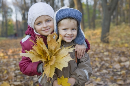 preteen boy: Brother and sister holding leaves in park portrait LANG_EVOIMAGES