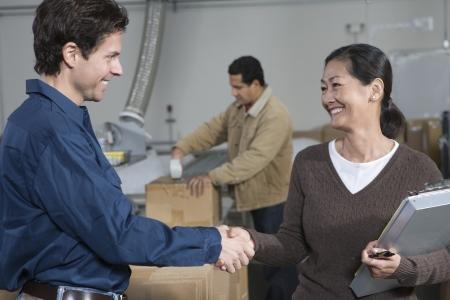 estrechando mano: Hombre y mujer que sacuden las manos en el almac�n de distribuci�n LANG_EVOIMAGES
