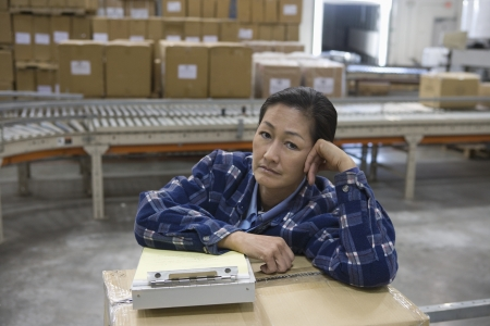 bored woman: Bored woman in distribution warehouse LANG_EVOIMAGES