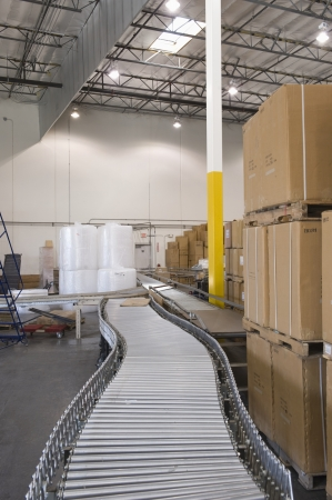 cinta transportadora: Cajas de cartón y cinta transportadora en el almacén de distribución