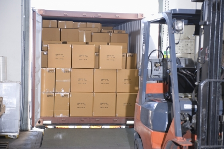 loading bay: Cardboard boxes and fork lift truck in distribution warehouse LANG_EVOIMAGES