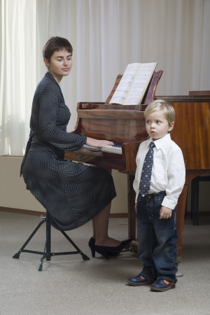 child singing: Boy (3-4) singing accompanied by teacher playing piano