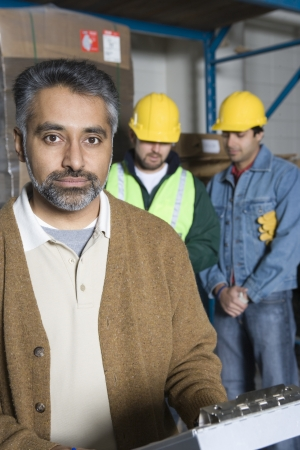 three day beard: Serious men in factory colleagues in background