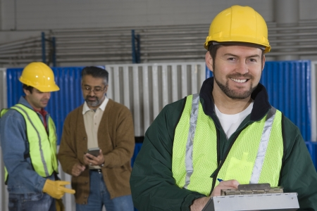 three day beard: Cheerful man standing in factory colleagues in background LANG_EVOIMAGES