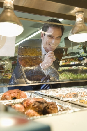 meat counter: Mature man grins through glass of meat counter in supermarket