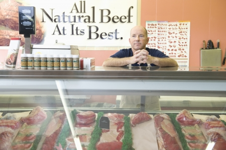 meat counter: Supermarket employee stands at meat counter in supermarket LANG_EVOIMAGES