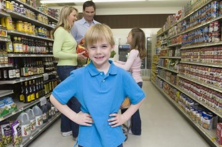 El muchacho se coloca con las manos en las caderas con familia de compras en el supermercado